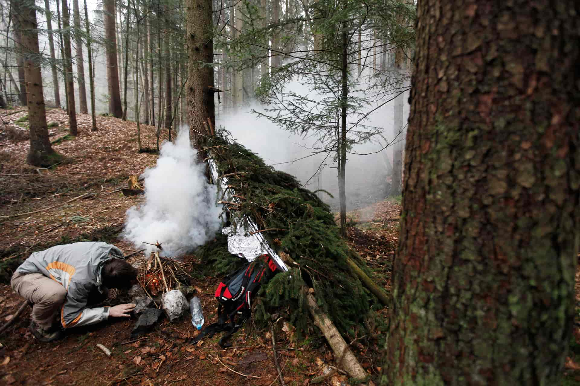 Man starting a fire near his survival lean to shelter