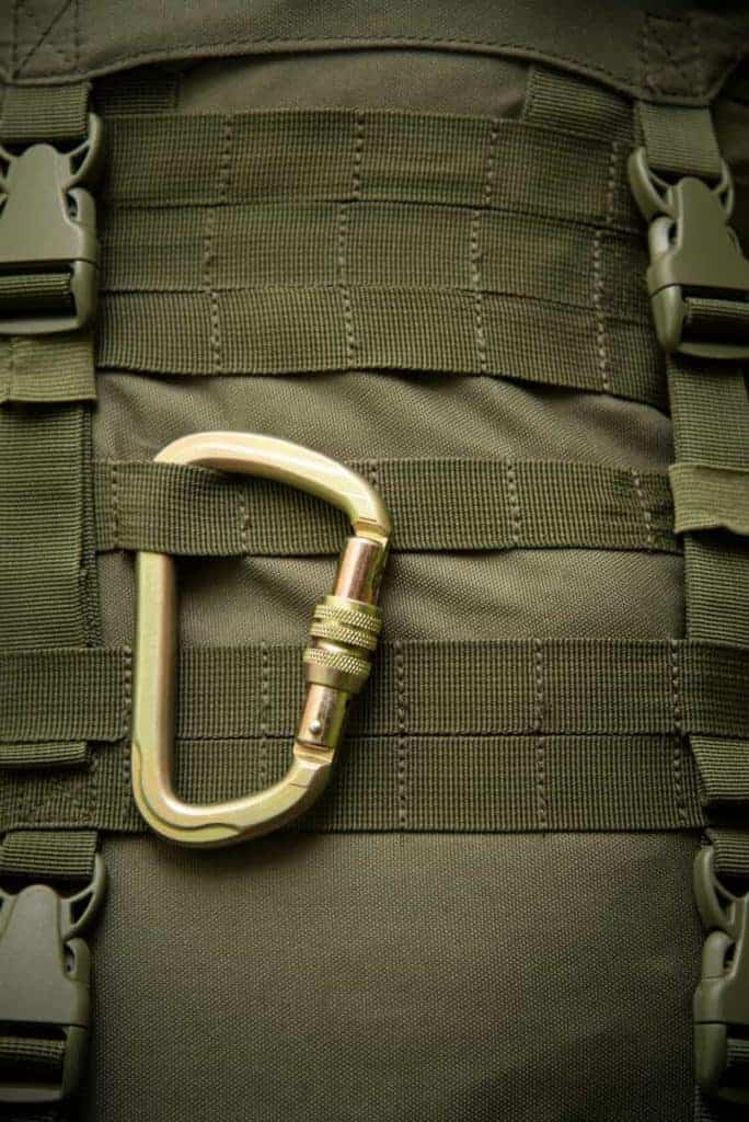 Carabiner strapped to a molle webbing on a backpack