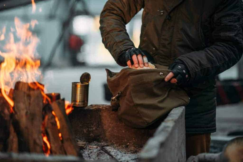 Survivalist eating bread and canned food by a fire