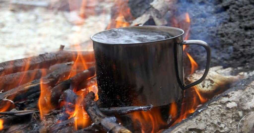 Cup with water boiling over a campfire