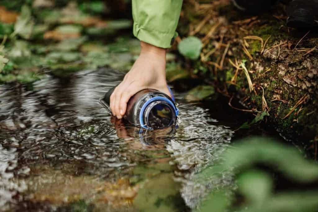 Person filling a water bottle from a creek