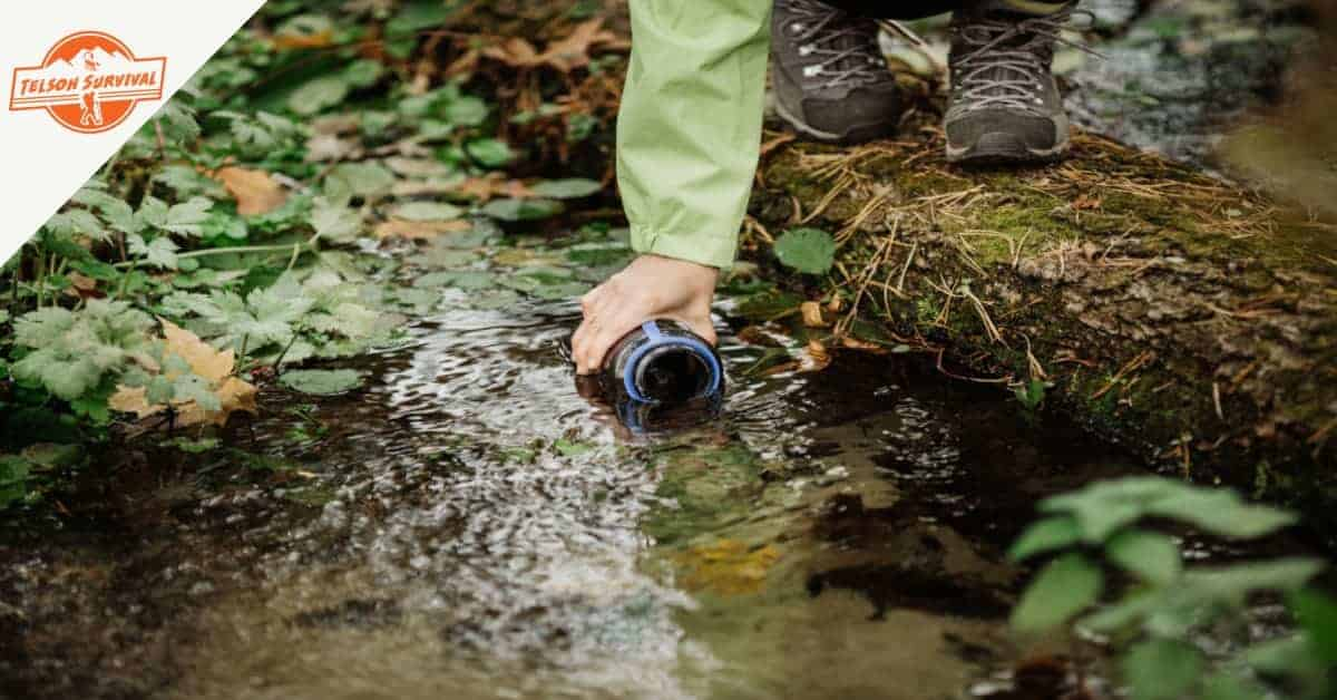 Woman using the best water filter to get drinkable water from a forest stream.