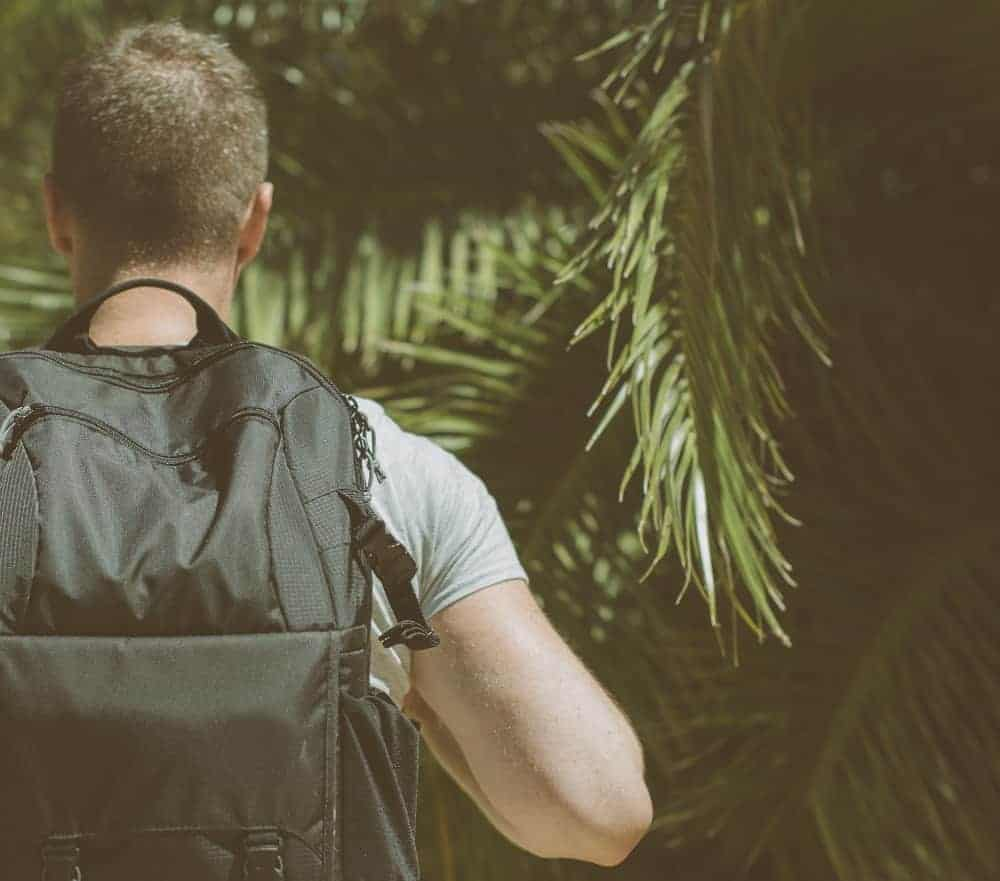 Man with backpack and light clothes walking into a jungle