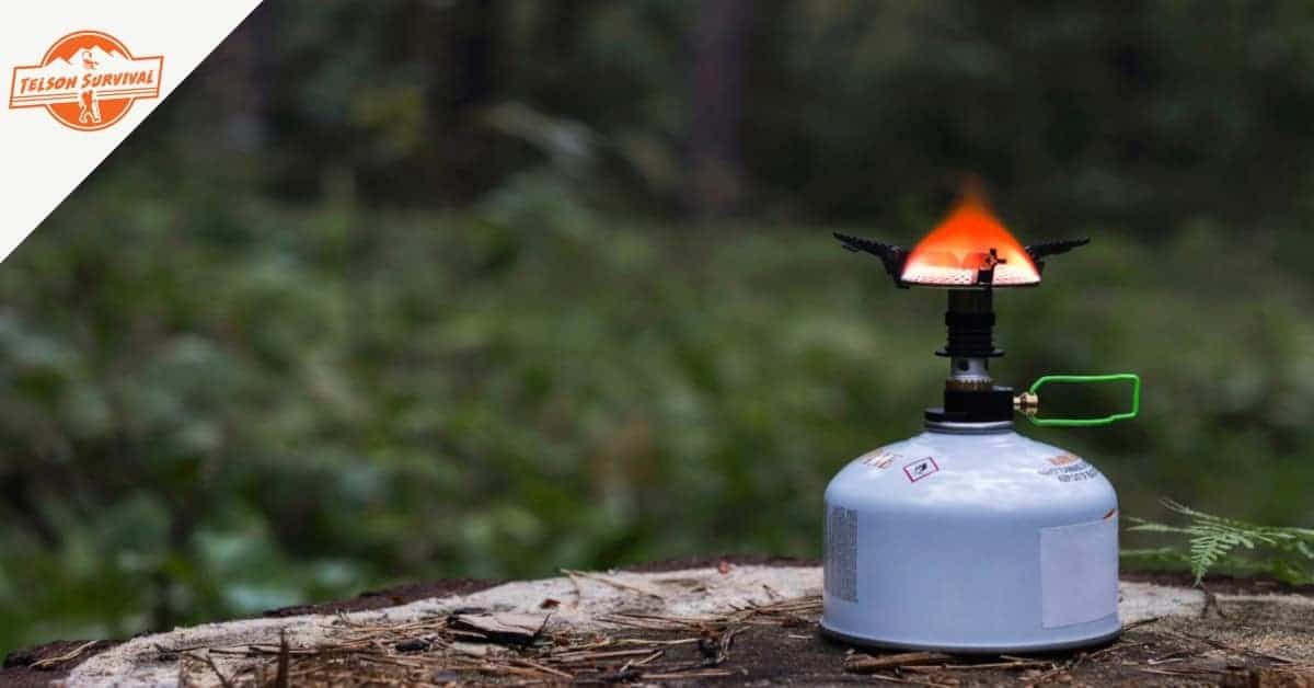 Portable survival stove burning in a wilderness background
