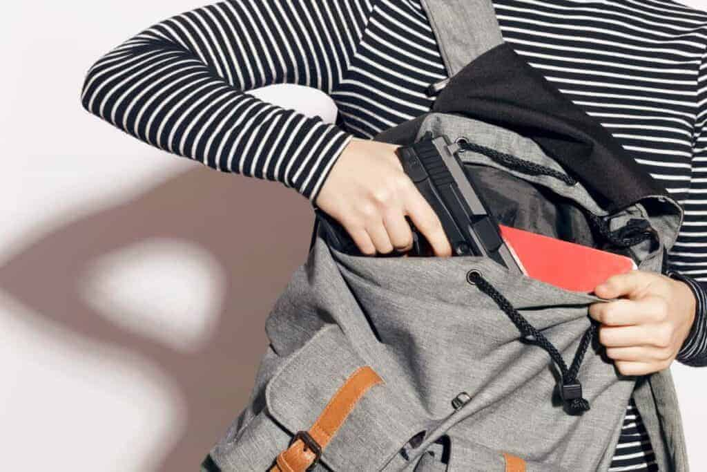 Gray woman carrying a concealed firearm in a gray woman backpack.