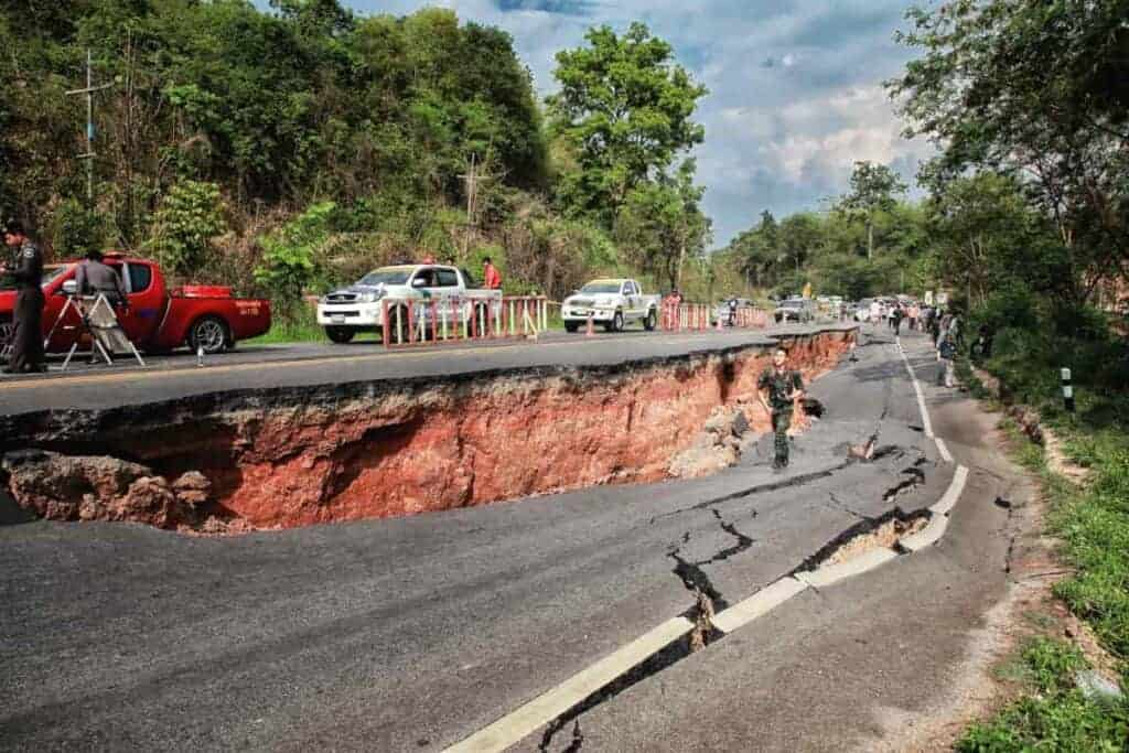 Cars moving on an asphalt road destroyed by a powerful earthquake