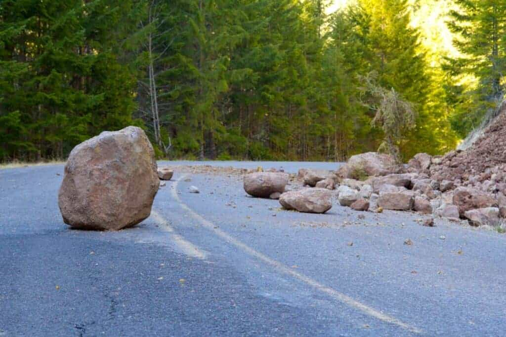 Boulders blocking a road in the aftermath of a landslide