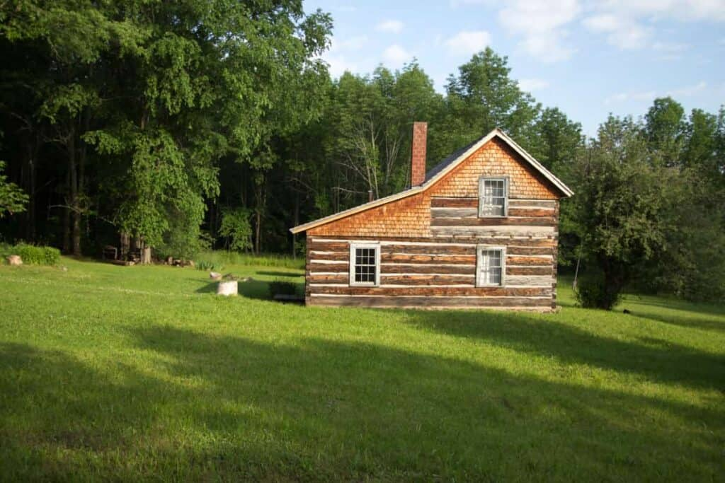 An off grid log cabin in a forest clearing